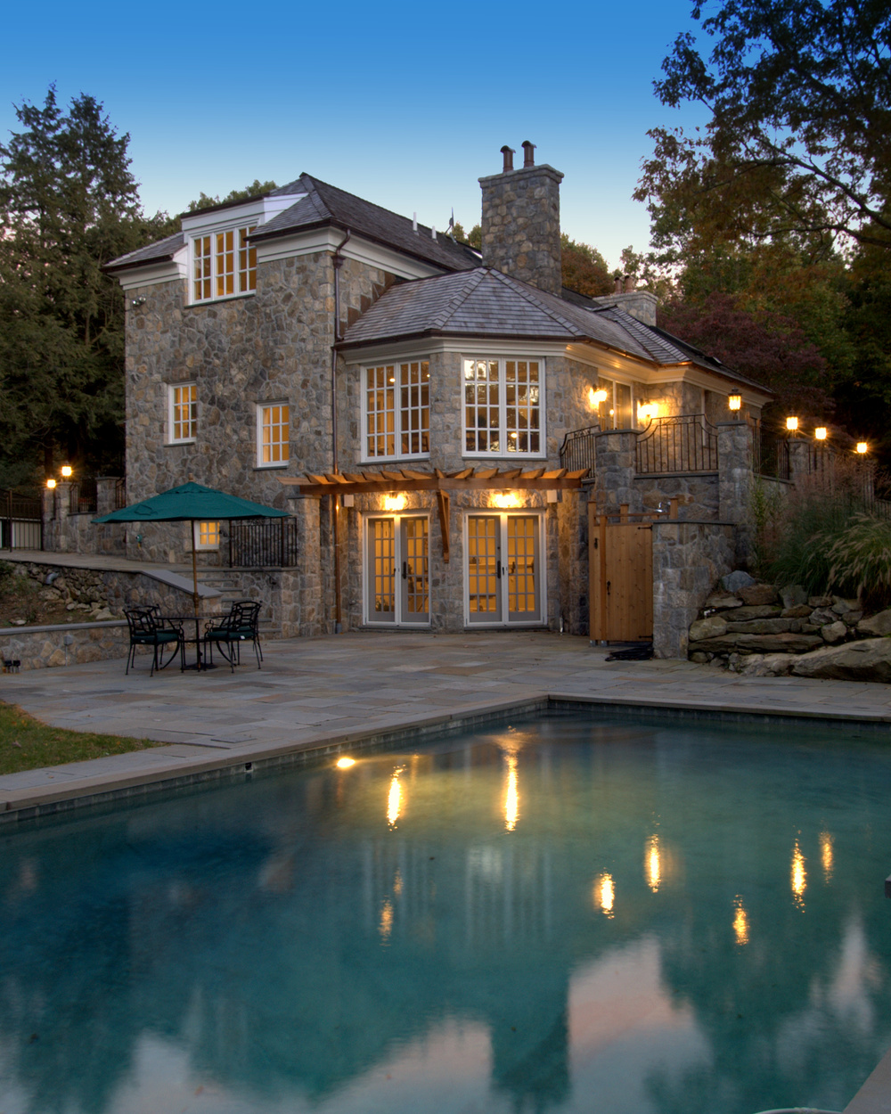 The original plan was to clad the house with purchased stone veneer, but to the delight of the owner, excavation for the new basement level found solid granite schist. The stone was harvested, and used to clad the entire house - on-site - by skilled masons.