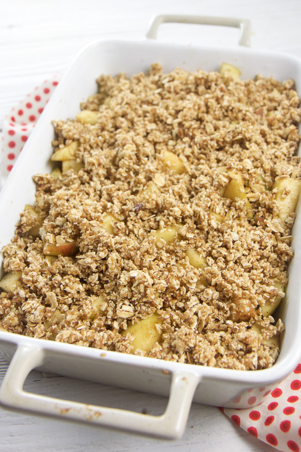 This Apple Pecan Crisp is bubbling over with spiced tender apples swimming in a caramel sauce all topped with a thick layer of crispy oat and pecan crust. Serve with a dollop of coconut whipped cream or vanilla bean ice cream for a healthy and kid friendly family dessert. #dessert #healthybaking