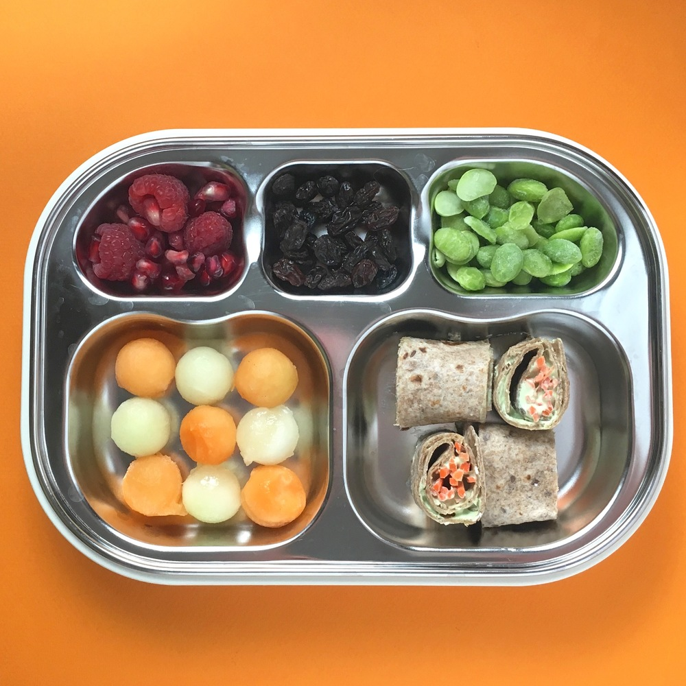 Zucchini + chive cream cheese with carrot rolls ups on whole wheat tortilla, mellon balls, raspberry + pomegranate seeds, raisins and frozen edamame.