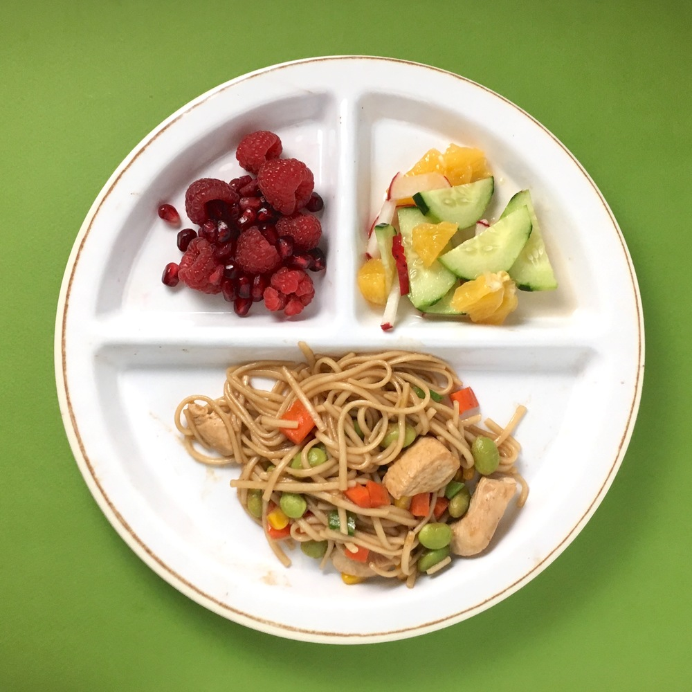 Sesame chicken + veggies with noodles, raspberry + pomegranate seeds finger salad, cucumber + radish + orange salad.