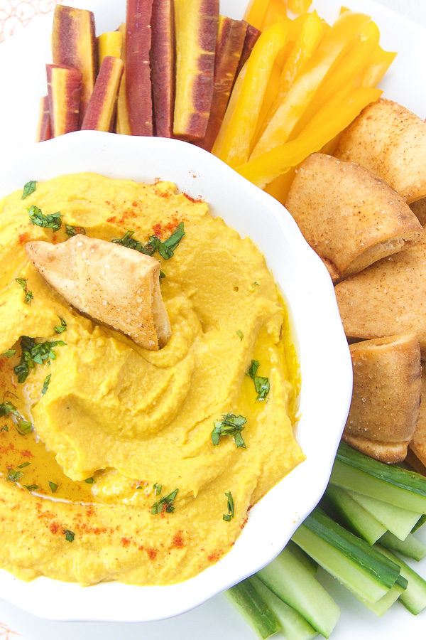 This Carrot Hummus is the perfect healthy snack for kids, toddlers, baby led weaning, and mom and dad too! It's made with 7 simple ingredients and a jar of Beech-Nuts carrot puree, which makes for a flavorful, smooth and healthy dip. Serve with crispy homemade spiced pita chips and a side of sliced vegetables and you have yourself a healthy kid-friendly snack the whole family will enjoy! #kidfriendly #snacks