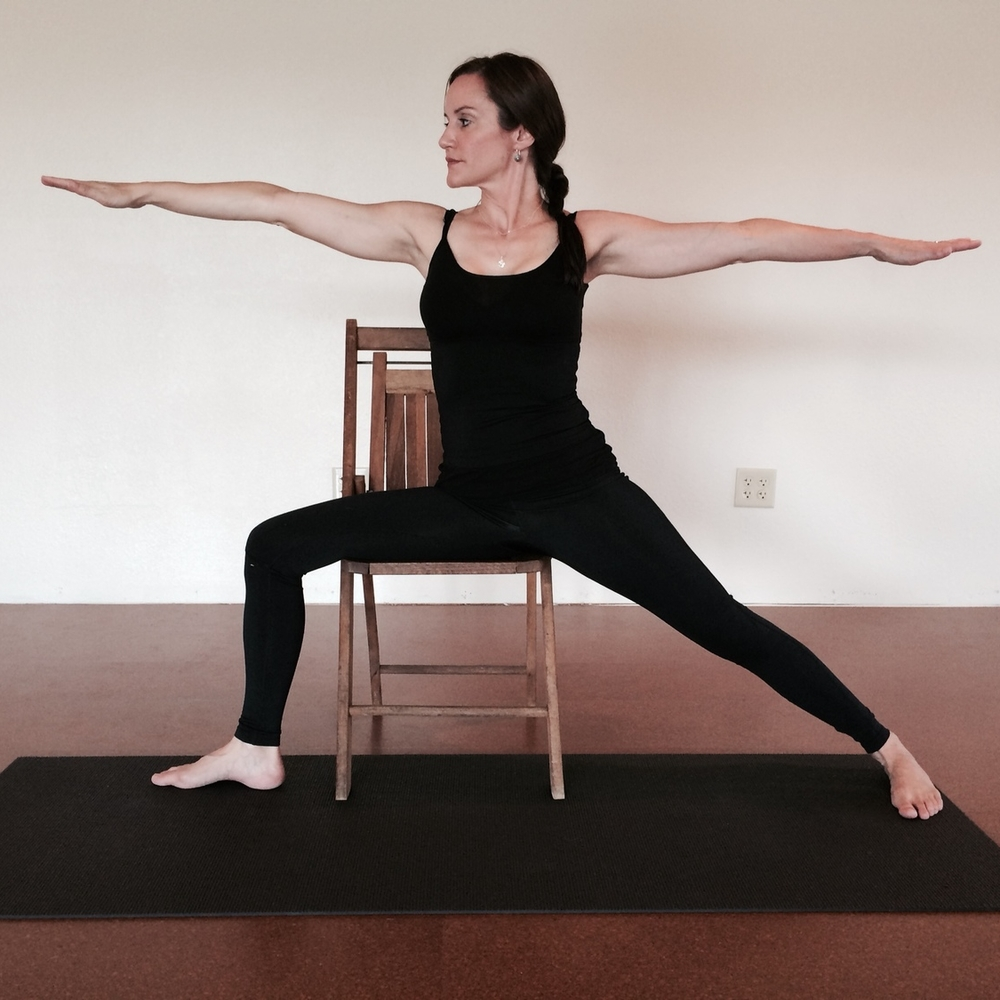 Warrior II with the front thigh supported by a chair. Students may need blankets to bring the thigh high enough that the hips can be level.