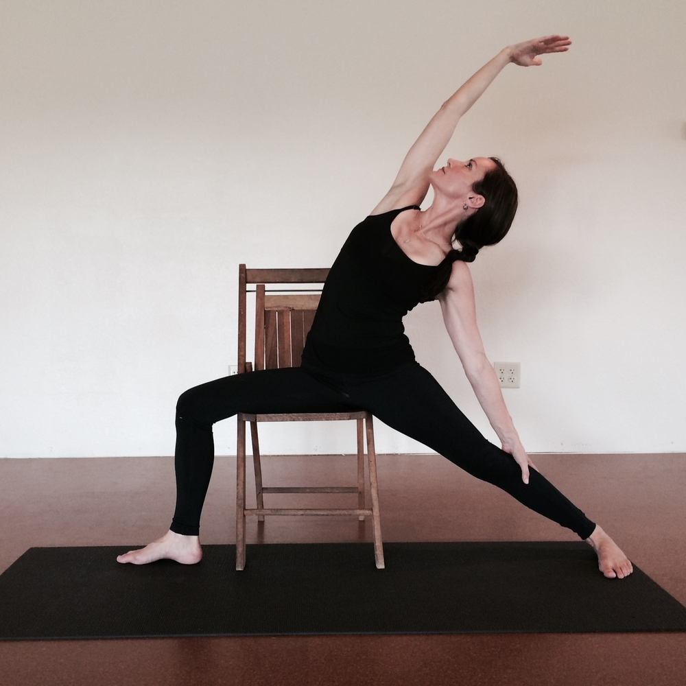"""Reverse Warrior"" variation to lengthen the side body and mid- to upper-back, using an optional chair for support."