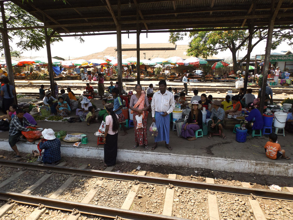 A market at a train station along the Yangon commuter train loop