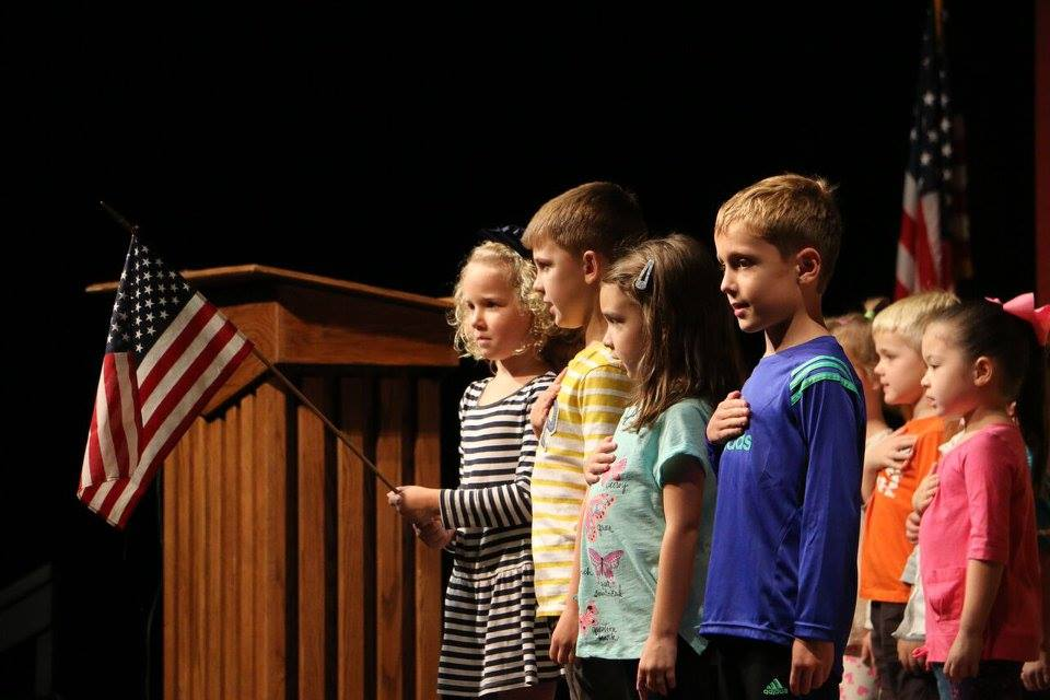 Students recite the pledge of allegiance at daily chapel, held in the auditorium.
