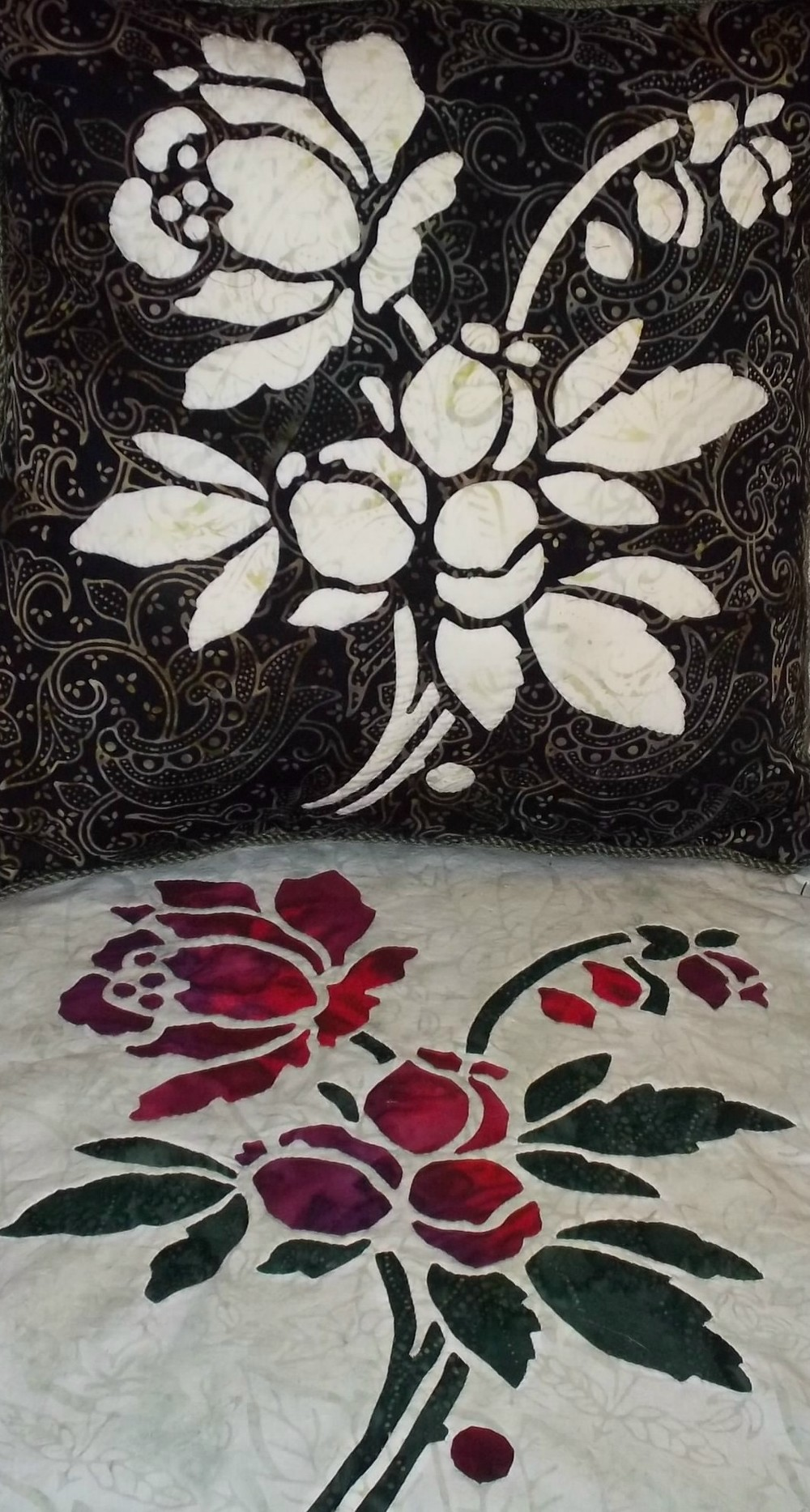 "Rose pattern in batiks. top picture: 16"" x 16"" pillow with reverse needle turn applique. bottom picture: 16"" x 16"" block employing appliqued blossoms on a top of reverse appliqued stems and leaves."