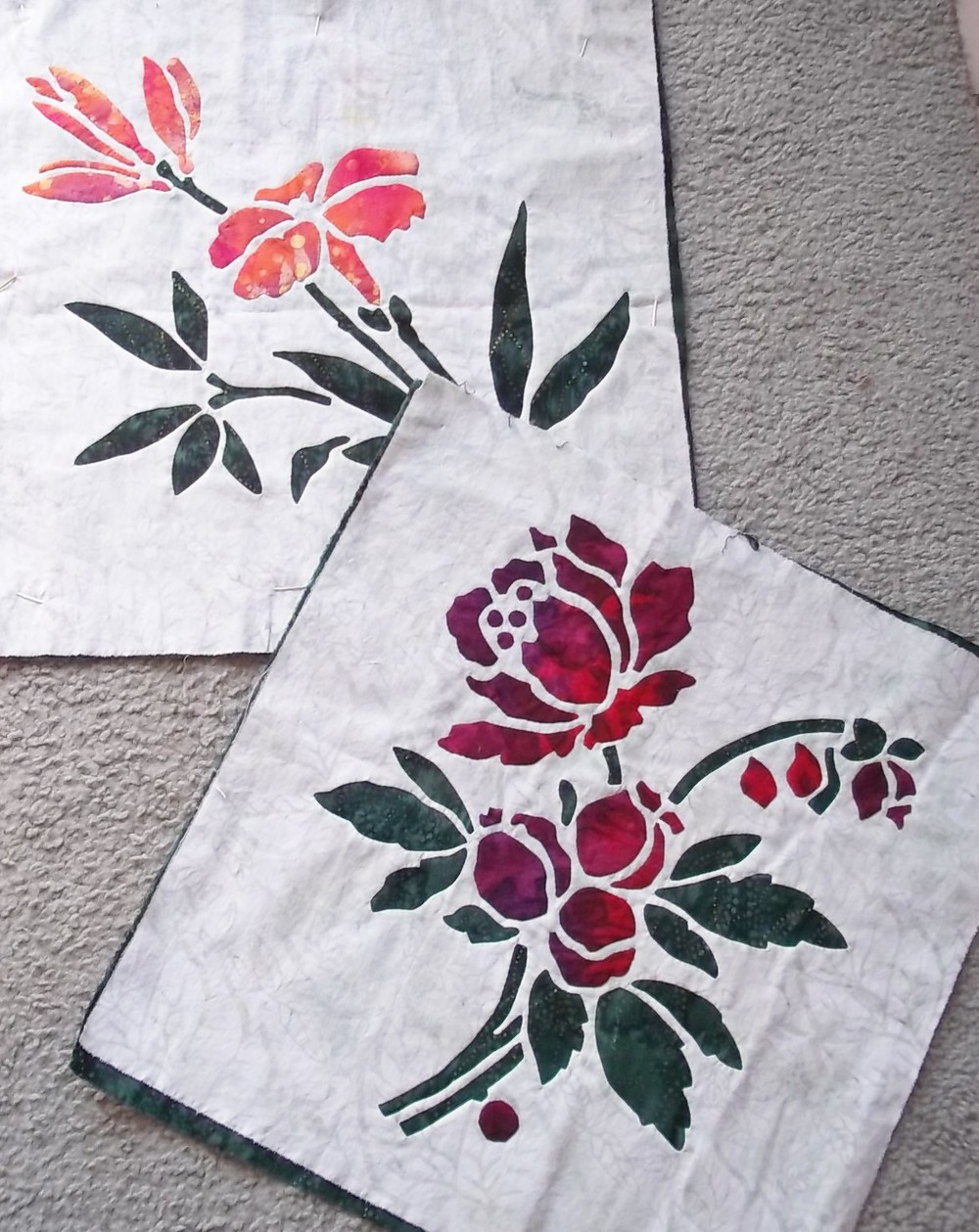 """Lily    ( 1 of 9),    Rose    (2 of 9). 16"""" x 16"""" blocks made with option 3: reverse applique stems and leaves with applique blossoms."""