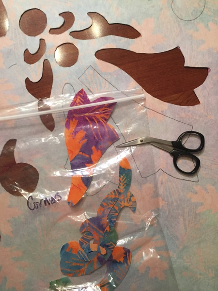 Carefully cutting the shapes out with my Kai sharp scissors, and organizing them in a baggie for use on the borders.