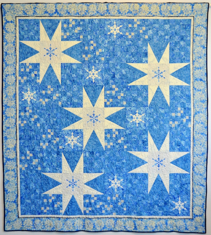 "Twinkling Flurries Quilt VI   (76"" x 84""). hand or machine reverse applique and machine pieced. Designed for Island Batiks Fall 2016. Published in Fons & Porter's Holiday Issue, Oct. 2016."
