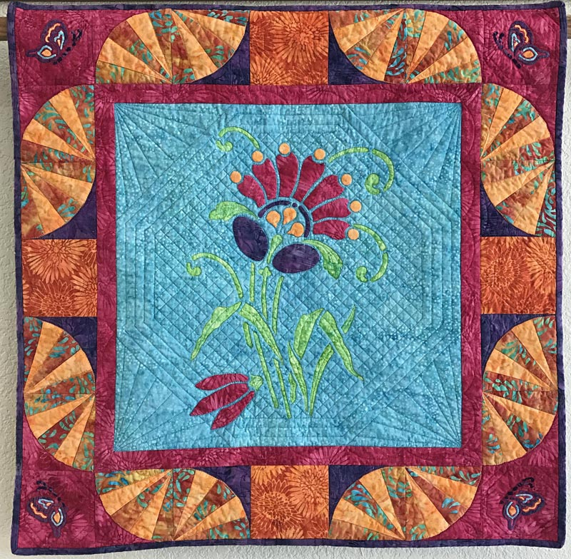 "Amidala's Flower mini-quilt   (28"" x 28""). hand or machine reverse applique with applique and machine pieced. Designed for Island Batiks Spring 2017."
