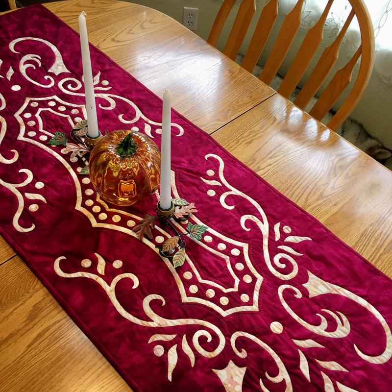 "Abounding Grace table runner VIII   (20"" x 56""). Hand reverse applique. Designed for Batik Textiles Fall 2016."