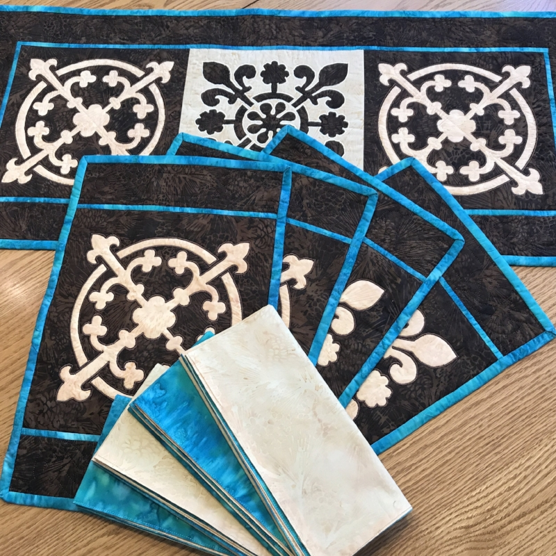"""Yorkshire Pudding table decor set  . table runner (14"""" x 32""""); place mats (10"""" x 15""""); reversible napkins (18"""" x 19""""). Hand or machine reverse applique. Designed for Island Batiks, fall 2017."""