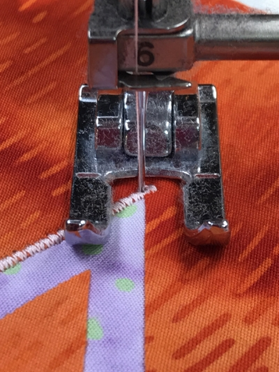 4. Pivot piece a bit more to the right so the presser foot is perpendicular to the un-stitched leg of the acute inside point. Lower the presser foot and sew.