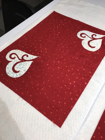 Layer red place mat top with quilt batting and backing for appli-quilting. Hold layers together with spray adhesive. I used 505.