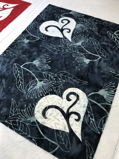 Layer black place mat top with quilt batting and backing for appli-quilting. Hold layers together with spray adhesive. I used 505.