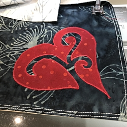Charcoal gray side of napkins.Reverse applique red heart onto 2 napkins with red Floriani embroidery thread.