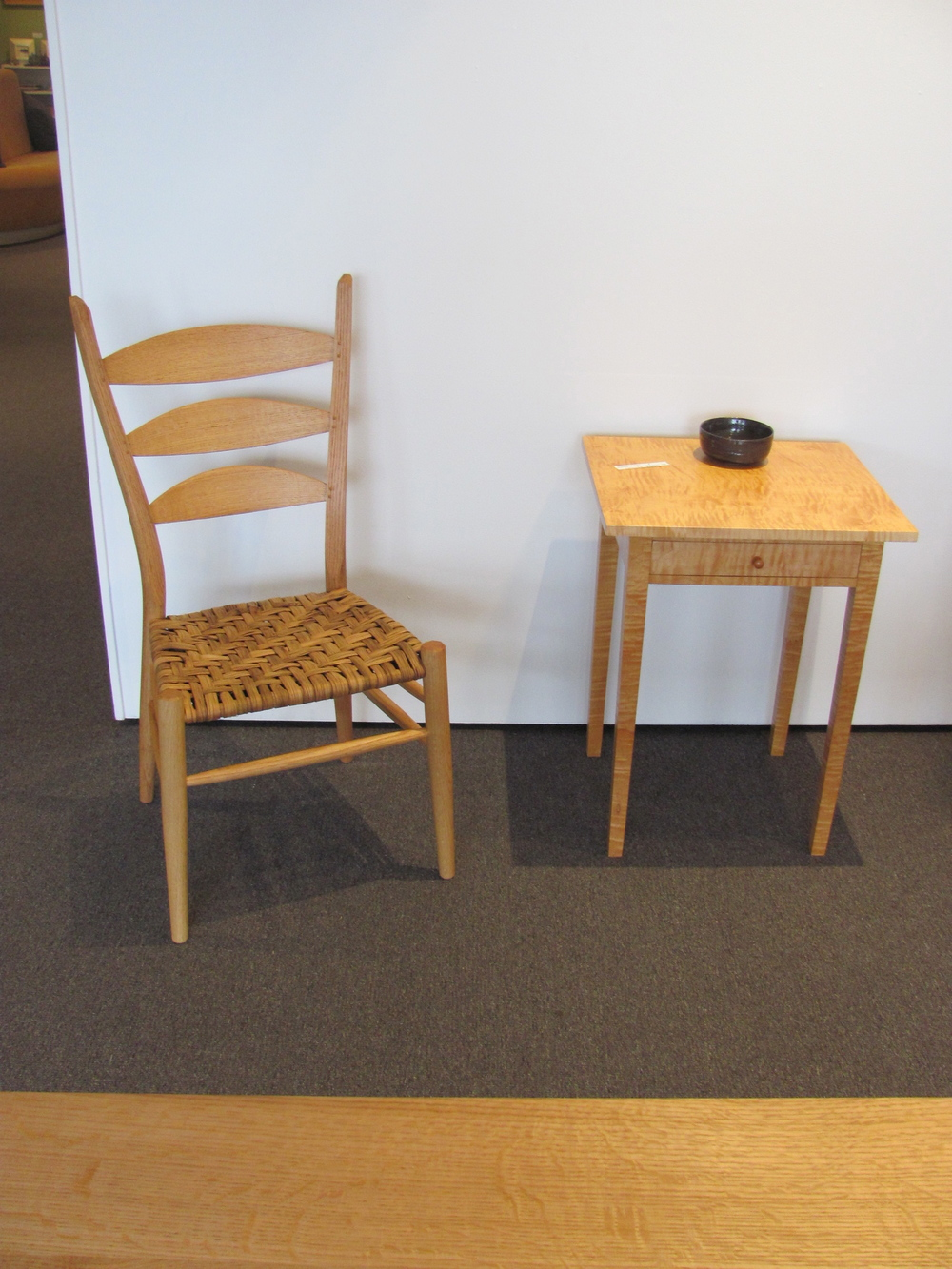A Boggs' post and rung chair in red oak and a very curly maple Shaker end table (which sold at the exhibition). My daughter 16-year-old daughter Erika does pottery and had the opportunity to display some of her works.     Foreground is some of the stunning ray flake in the above red oak table.