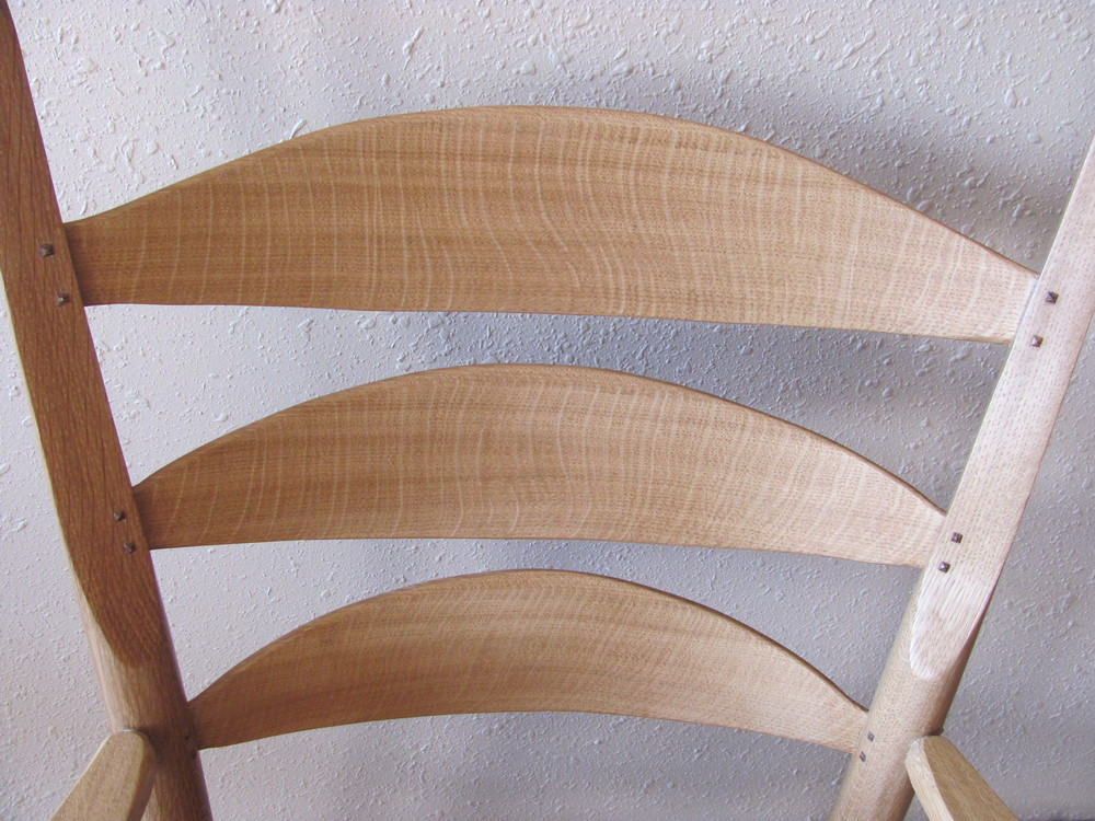 The medullary ray flake of the oaks is stunning. In this example of bur oak (a type of white oak), the ray flake gently sweeps your eye through a series of curves over the whole length of the back of the chair. This is oak at its finest--showing quarter-sawn grain. Too many people dismiss the oaks today because most of what they see is flat-sawn.  A princely wood, the oaks are hard to beat. Hardy, durable--they delight you with their natural coloring and their unique patterns of ray flake.  You can also add a quarter-sawn table top to pick up the themes in the slats, tying the whole set together beautifully.  This is an arm chair from the Porter set.