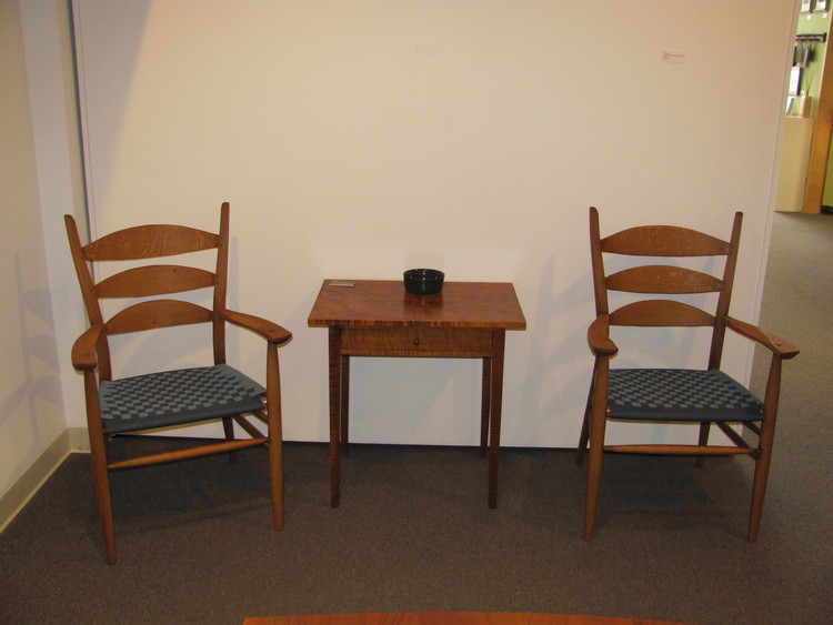 "A pair of Boggs' arm chairs and a Shaker end table. The chairs were sold going into the exhibition, but the client agreed to have them displayed. They chose a dark vintage stain to match a 150-year-old scrub top antique table. Glazes were added to give the appearance of age. ""These chairs are so comfortable,"" the client said, ""I like to pull  one over to the the lamp to sit in while reading in the evenings.."""