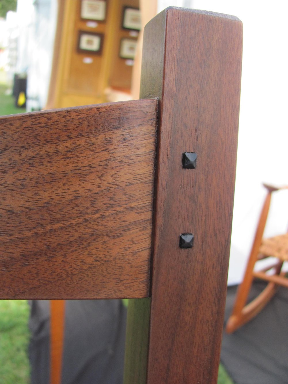 Close up of the quarter-sawn rail with shaped ebony pins. This set of eight chairs and matching table was a major draw at the 2017 Driftless Art Fair in Soldier's Grove, WI.