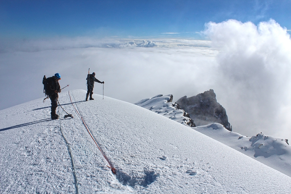 The team descends the glacier as heavy clouds begin swamping the upper mountain.