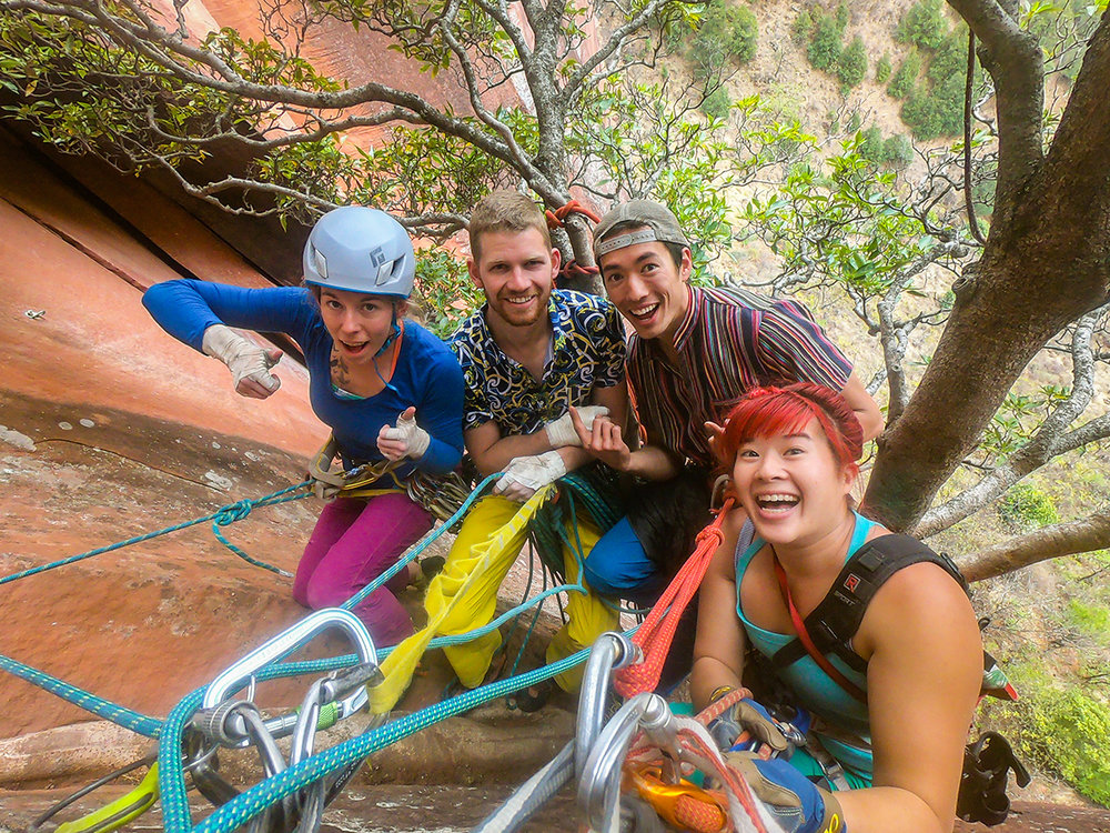Friends at the end of a great day. (left to right) Ashley Cracroft, Danny Parker, Ryder Stroud, and Irene Yee all ready to rappel to the ground for a good meal back in Liming village!  © Irene Yee/Lady Lockoff Photography