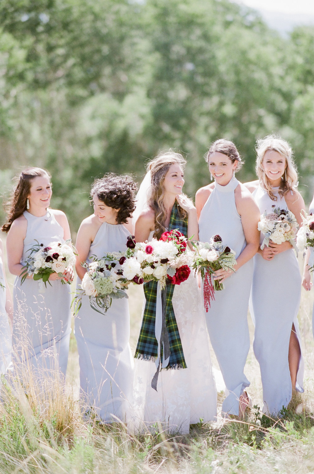 bride in telluride with red flowers and bridesmaids