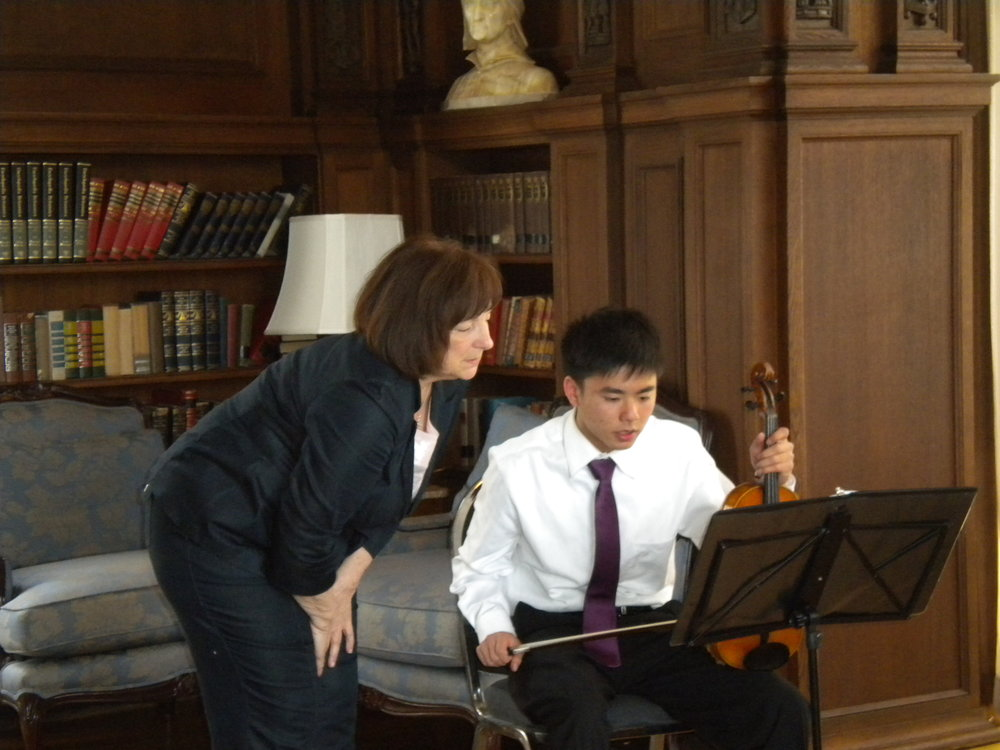 Director Susan Bates with violinist Tim Yu in the Kohl Mansion Library