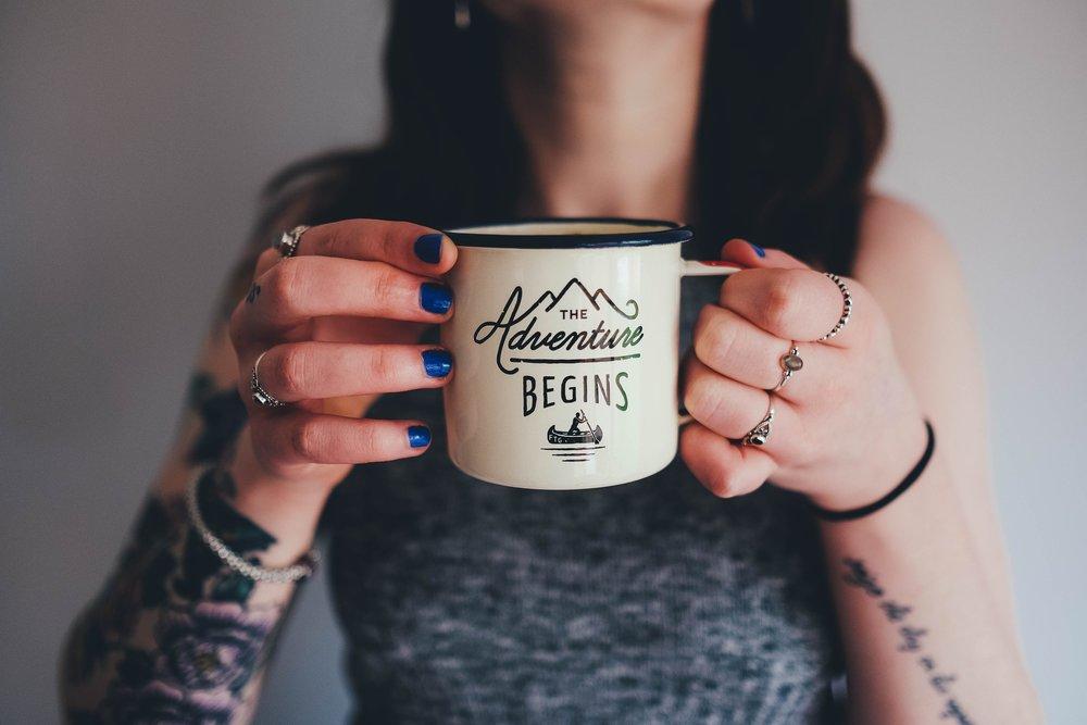 Adventure begins mug in womans hand.jpg