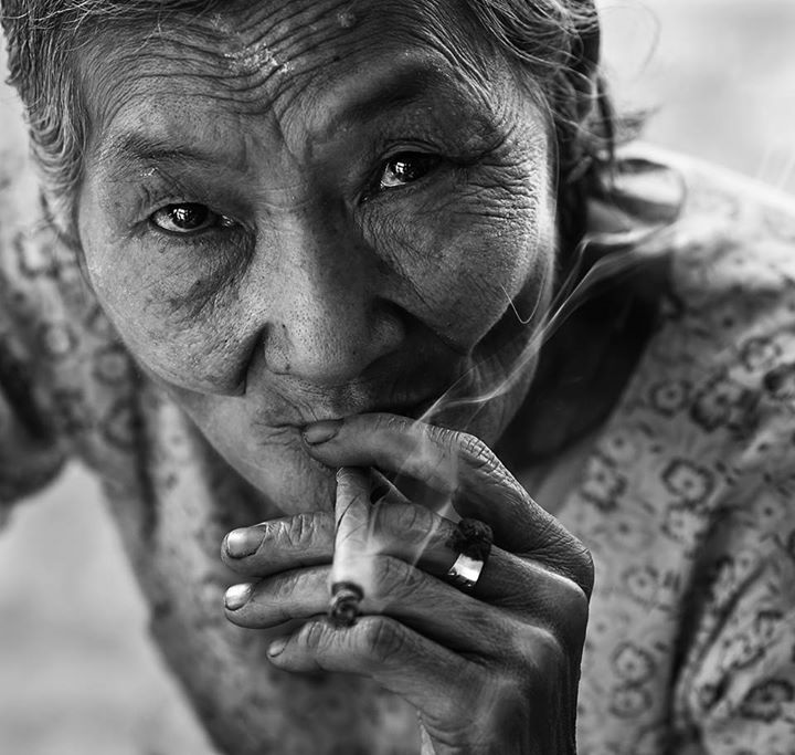 An old lady smoking a hand rolled cigarette in Myanmar