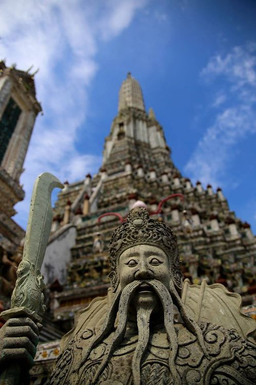 Stone guardian at Wat Arun in Bangkok by Drew Redmond