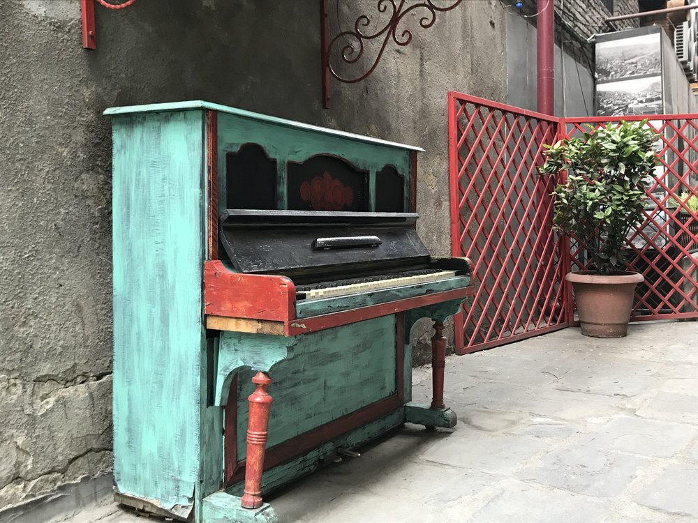 A painted piano, standing in the street