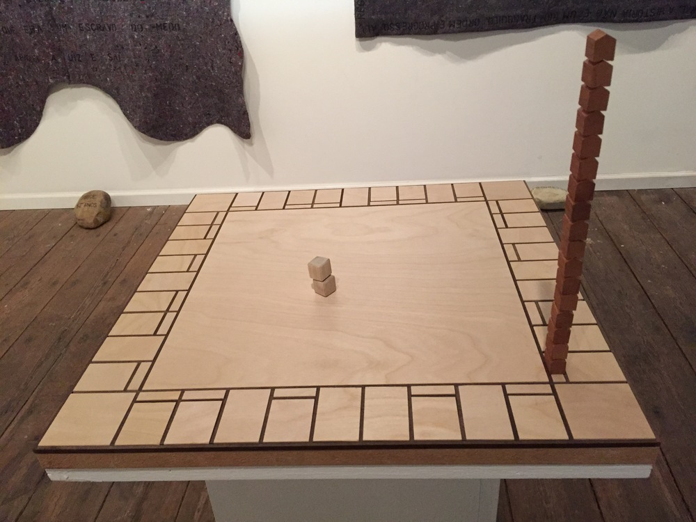 "Anthony Heinz May Eropoly Mahogany, Birch, Poplar, Masonite and MDF 2015 Statement: ""Most acquisition of information in early age comes from games that provide greater physiological understanding for competitive relationships involving loss and win. Cultural and societal belief drives these elements of victory into the definition for success, forming the first concepts of physical and mental real ity. This focus on achieving and gaining instead of nurturing mutual existence becomes a dangerous preoccupation created through oppression, inequality and social immobility - all dehumanizing terms that contribute to homelessness and marginalization of life. Outcomes of the game are defined before start of gameplay, so existence can only lie within the omnipresent and placated spectacle of human competition at the core."""