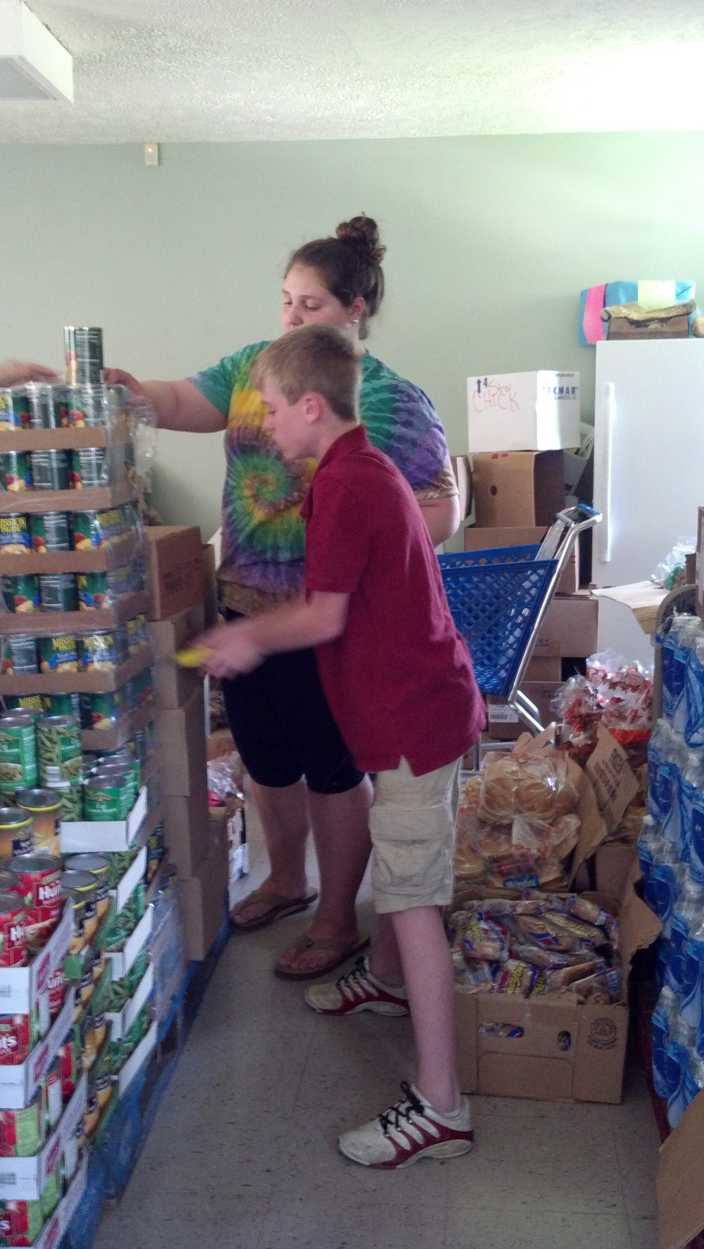 Two youth helping organize the food pantry.