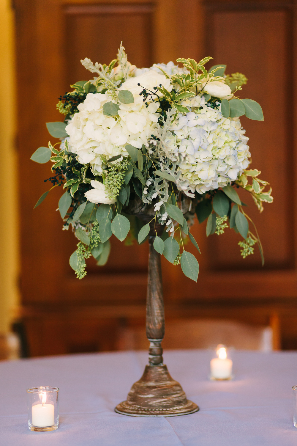 Elevated floral arrangement with blue and white hydrangeas, privet berries, and lush greenery