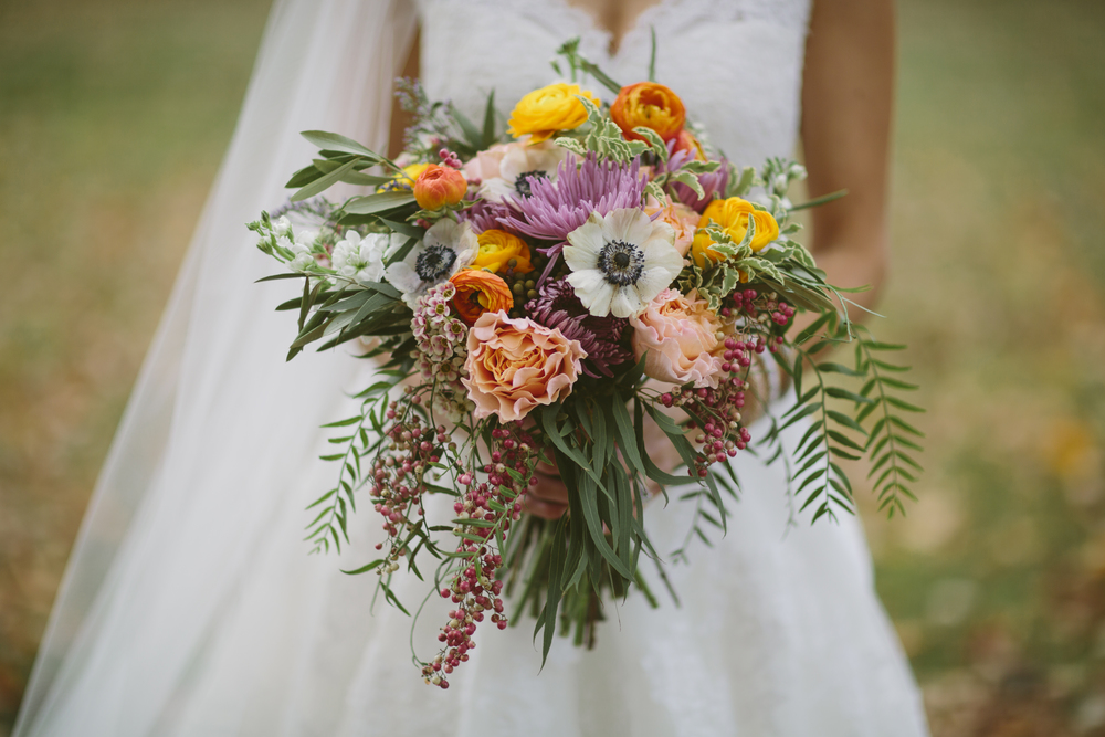 Colorful, bohemian bridal bouquet with anemones, orange ranunculus, peach garden roses, and greenery // Nashville Wedding Flowers