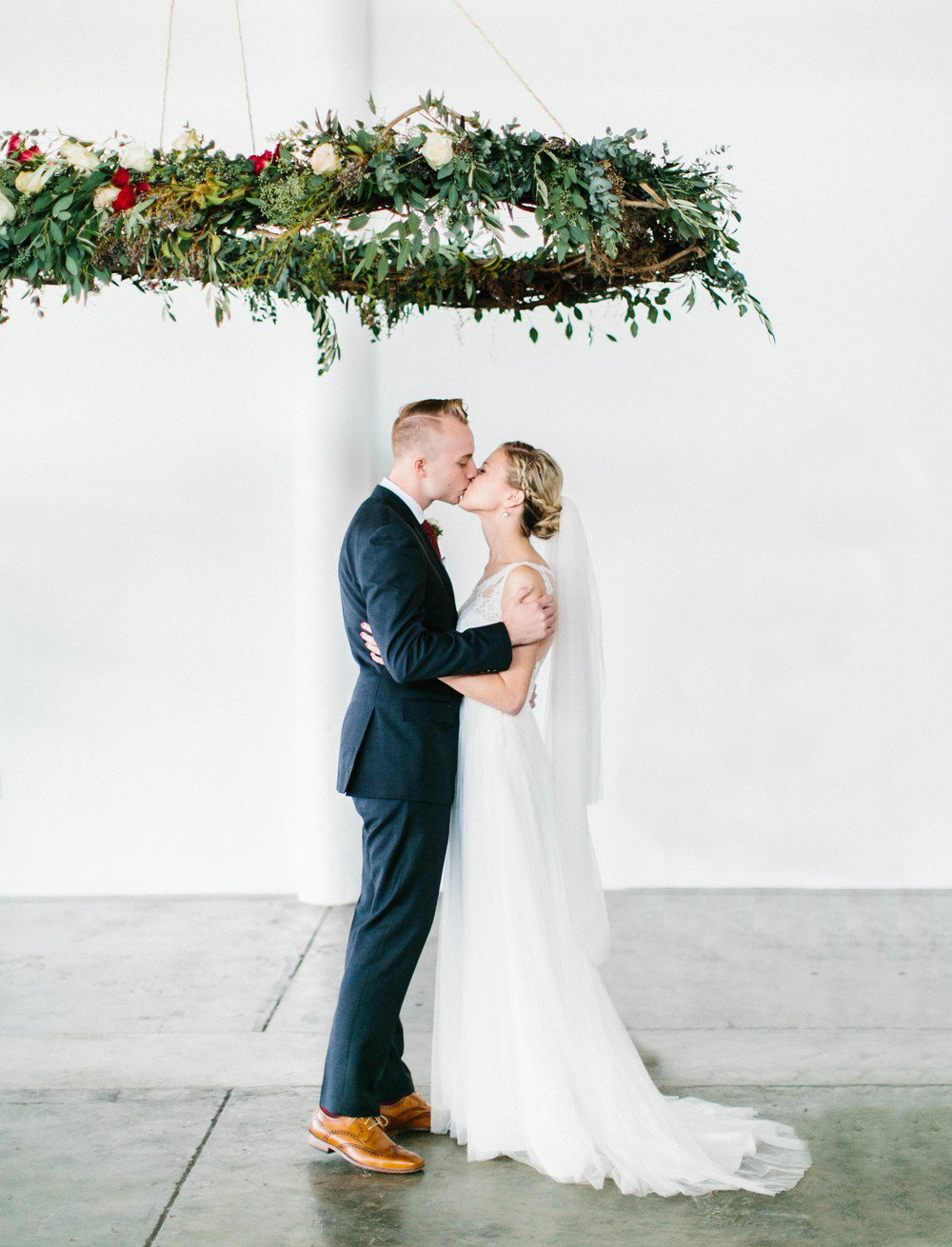 First Kiss under suspended floral wreath // Destination Wedding Florals