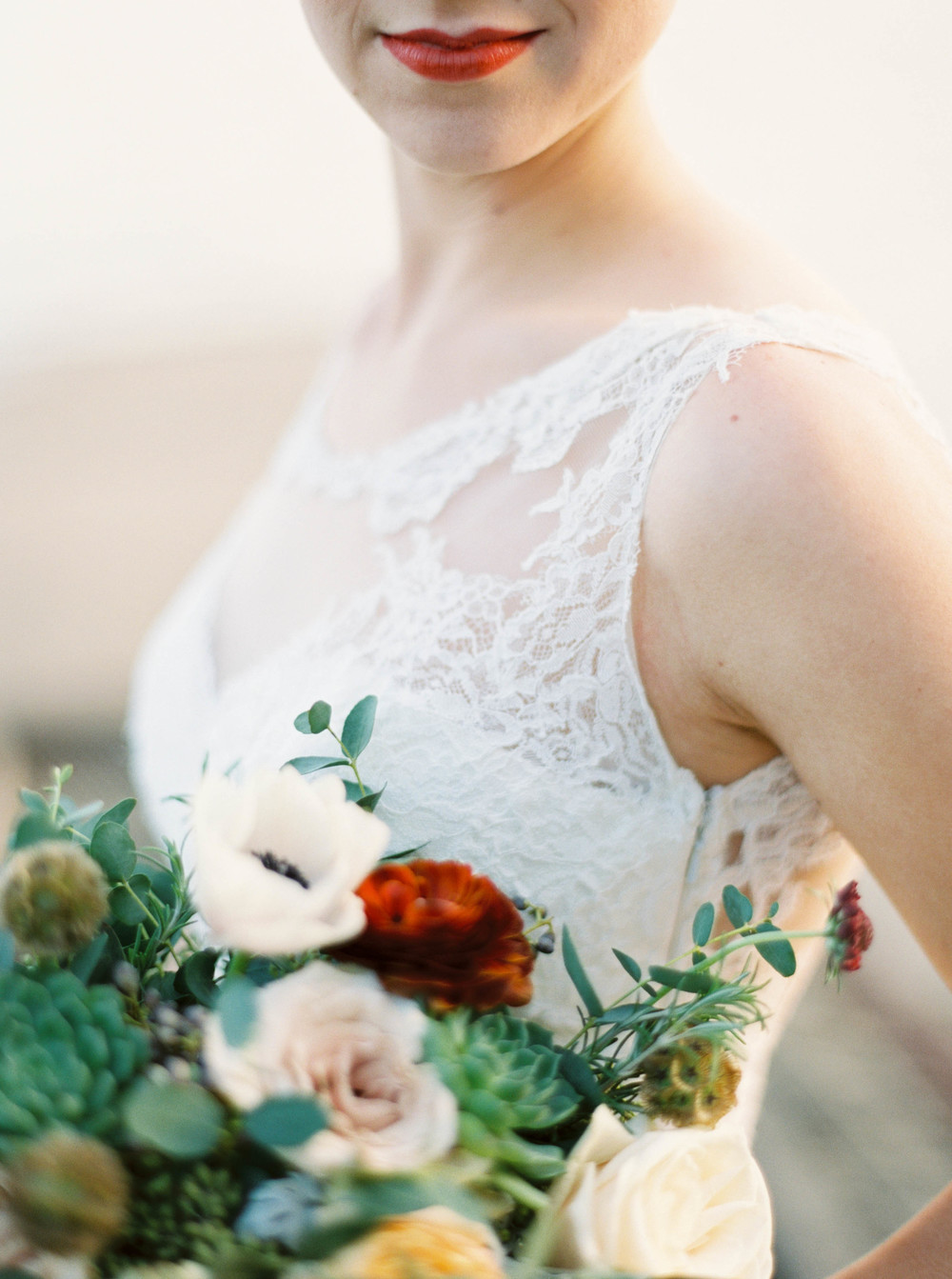 Loose, untamed bridal bouquet with olive branches, ranunculus, and succulents