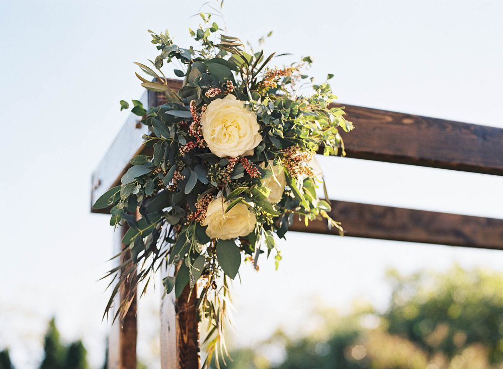 Rustic wooden chuppah with floral accents