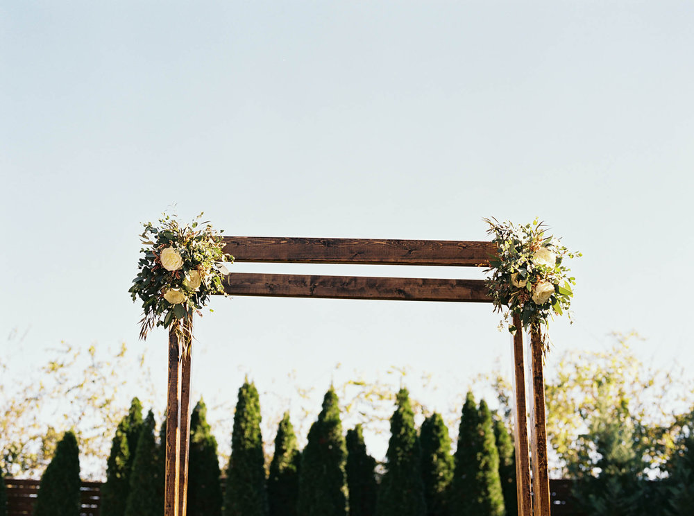Simple wooden chuppah with floral sprays // Nashville Wedding Florist