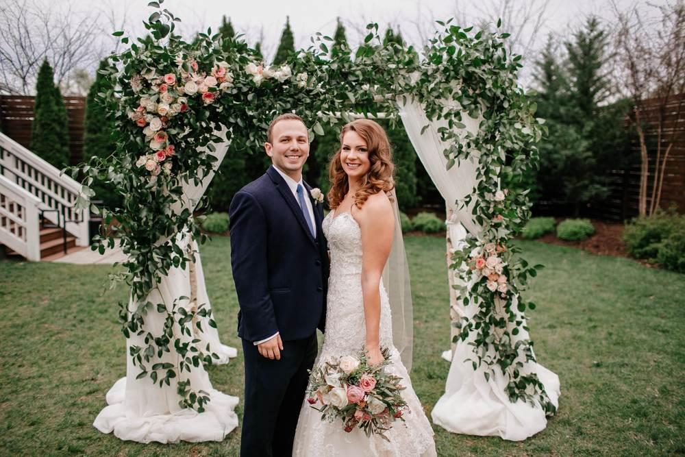 Loose, natural chuppah decor of lush greenery and roses // Nashville Wedding Flowers