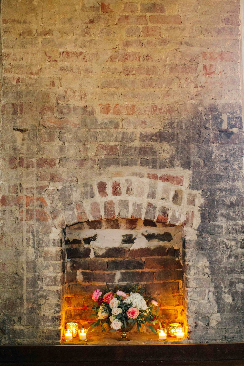 Floral arrangement in fireplace with candles // Blush and neutral Nashville Wedding flowers