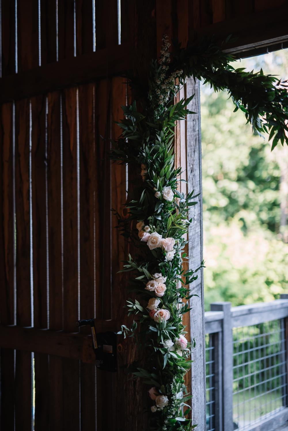 Garland with florals for rustic wedding ceremony backdrop