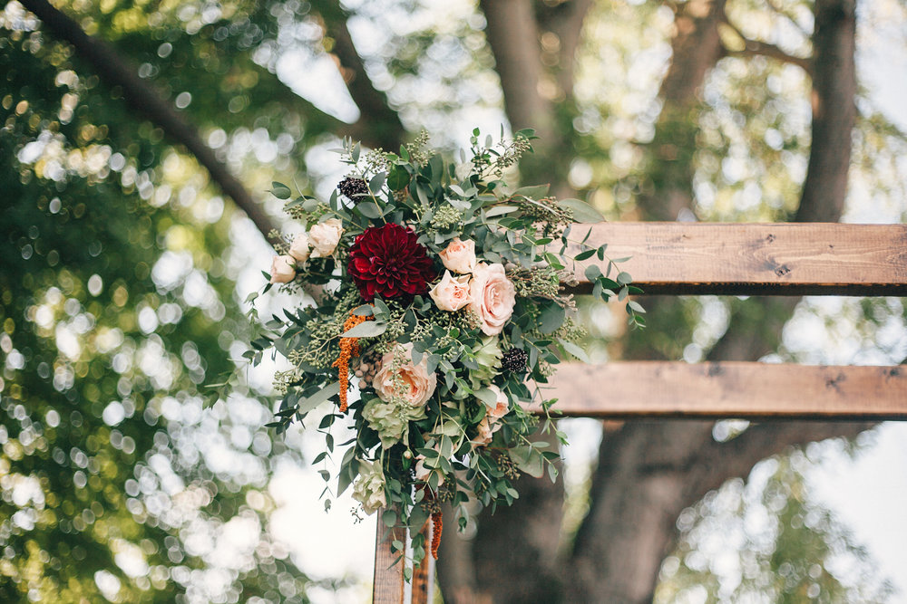 Simple chuppah style with loose greenery and pops of burgundy // Nashville Wedding Florist
