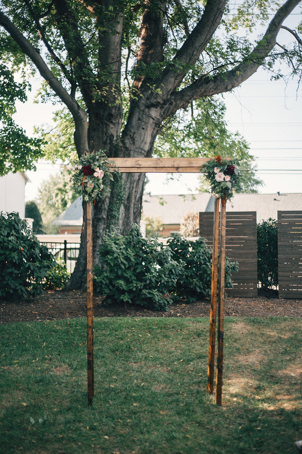 Simple wooden chuppah with burgundy, peach, gold, and greenery florals // Nashville Wedding Florist