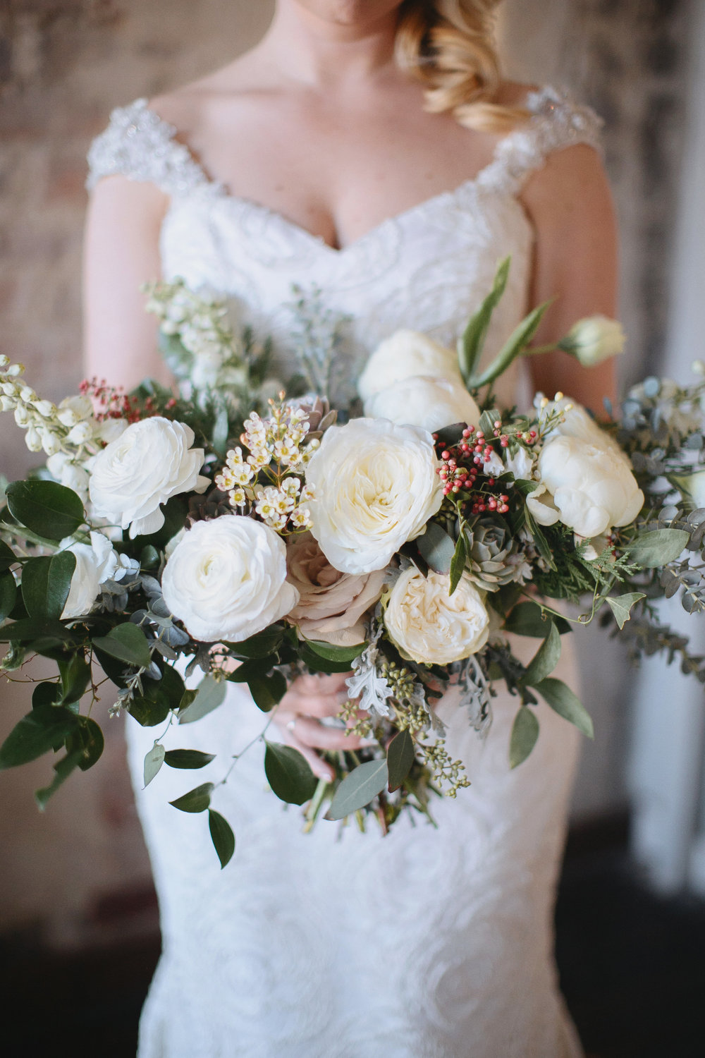 Wintry bridal bouquet with all white flowers, natural greenery, and touches of red berries // Nashville Wedding Florist