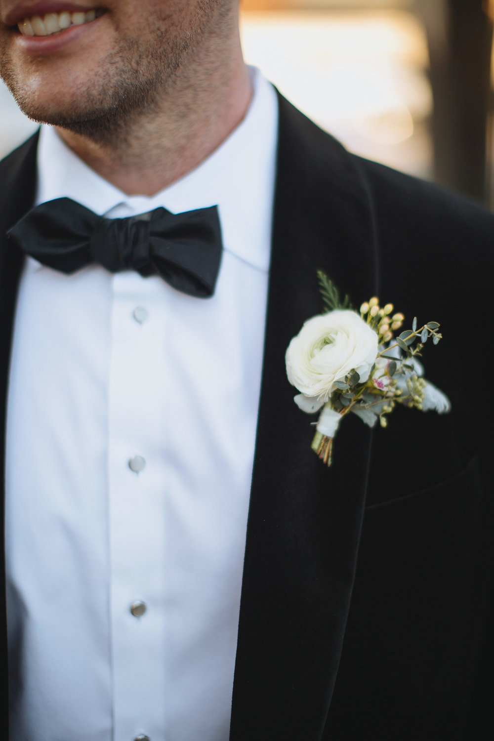 Wintry Boutonniere with evergreen, red berries, and a white ranunculus // Nashville Wedding Flowers