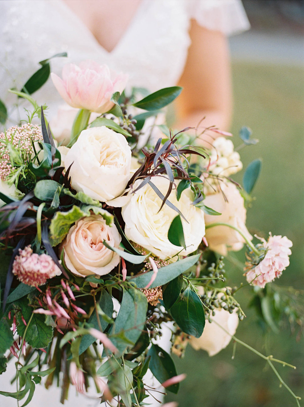 Lush, natural bridal bouquet with garden roses, tulips, blush ranunculus, and greenery in botanical garden // Southern Wedding Floral Design