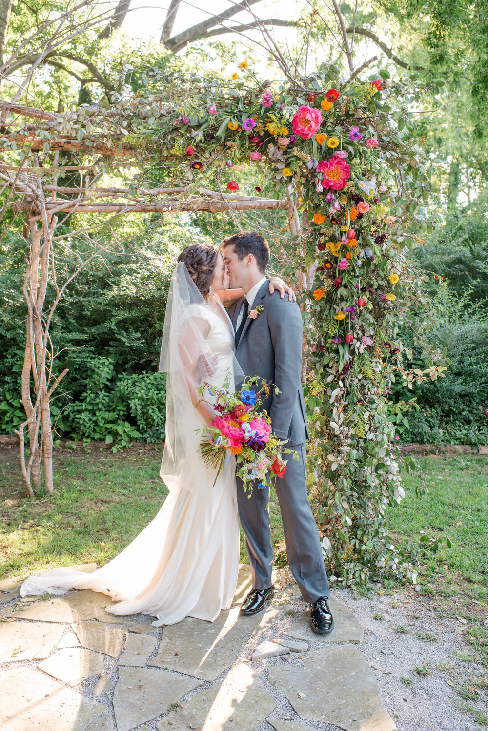 Lush, bright wedding ceremony arch with peonies and ranunculus // Chagall Painting Inspired Wedding Flowers