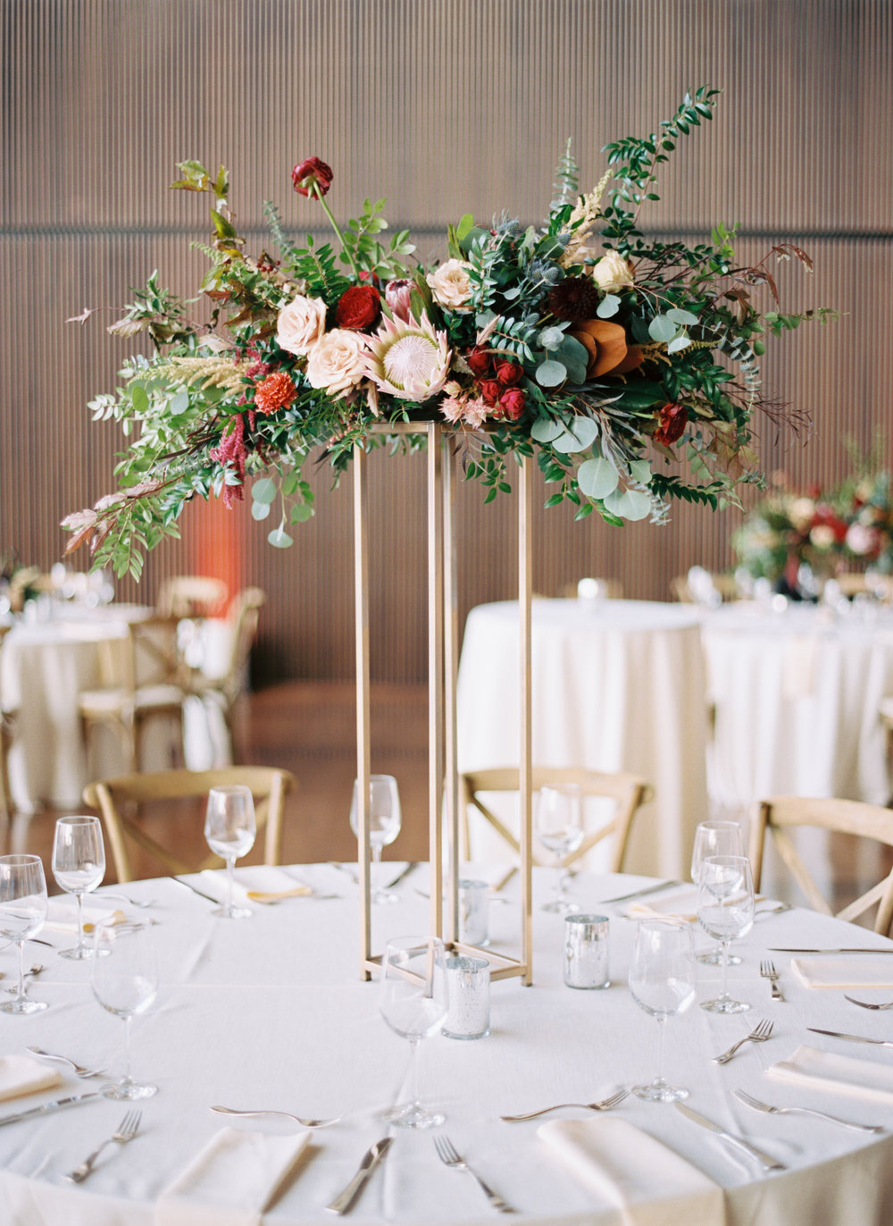 Blush and marsala centerpieces with protea, ranunculus, dahlias, and lush greenery // Country Music Hall of Fame Wedding, Nashville
